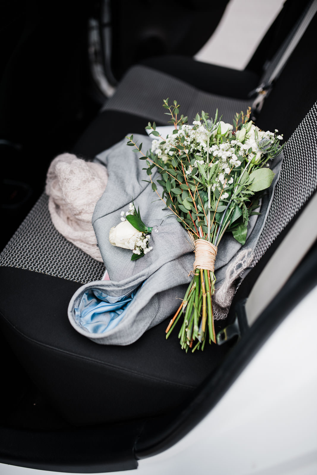 bouquet of flowers on rear car seat with blue jacket