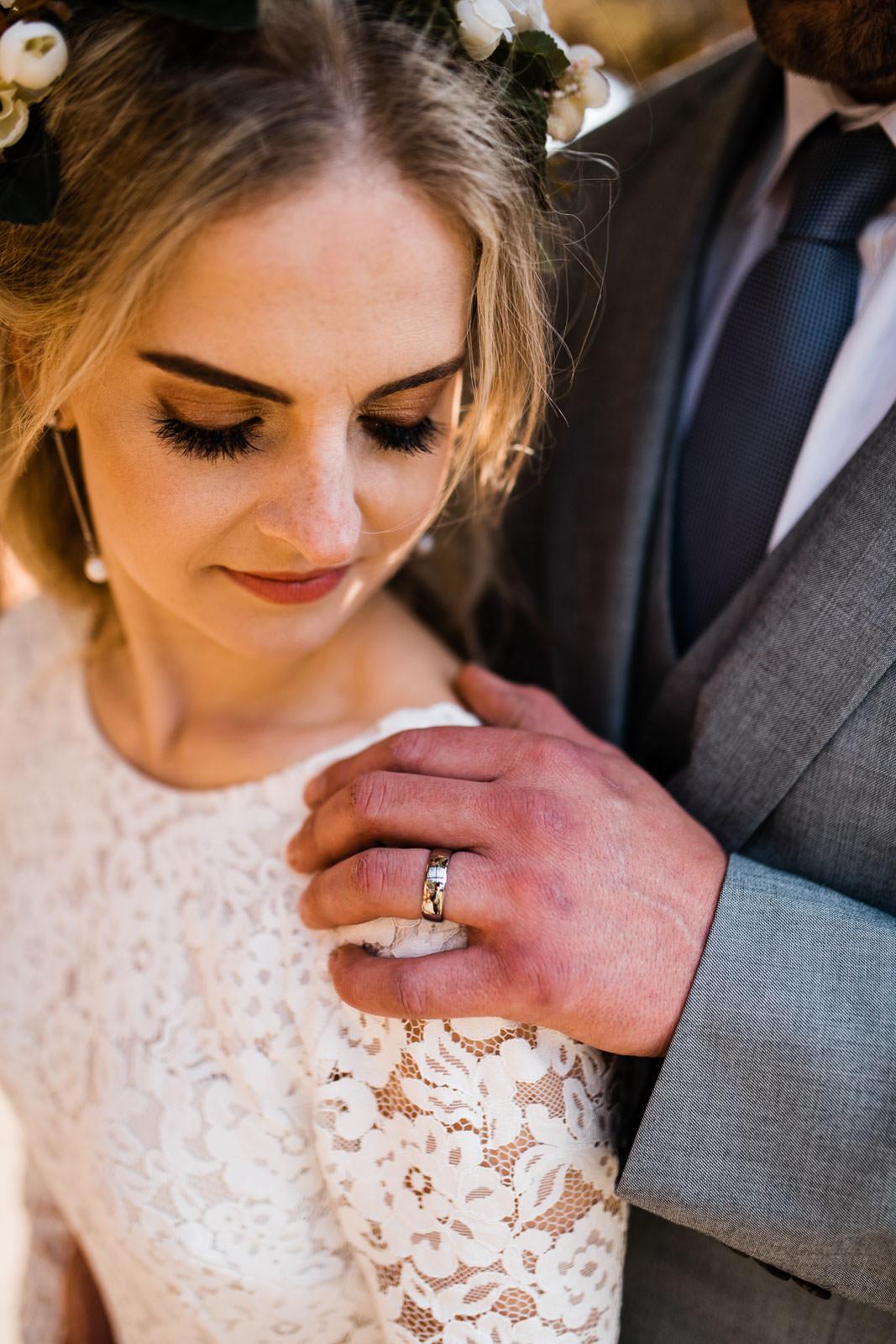 wedding ring on grooms hand and wedding dress