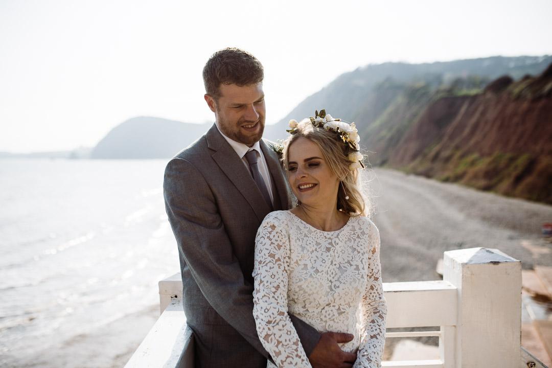 similing bride stood on coastline holding flowers