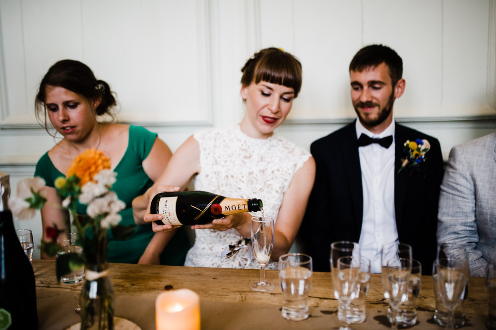 bride pouring a glass of chapaigne at wedding table