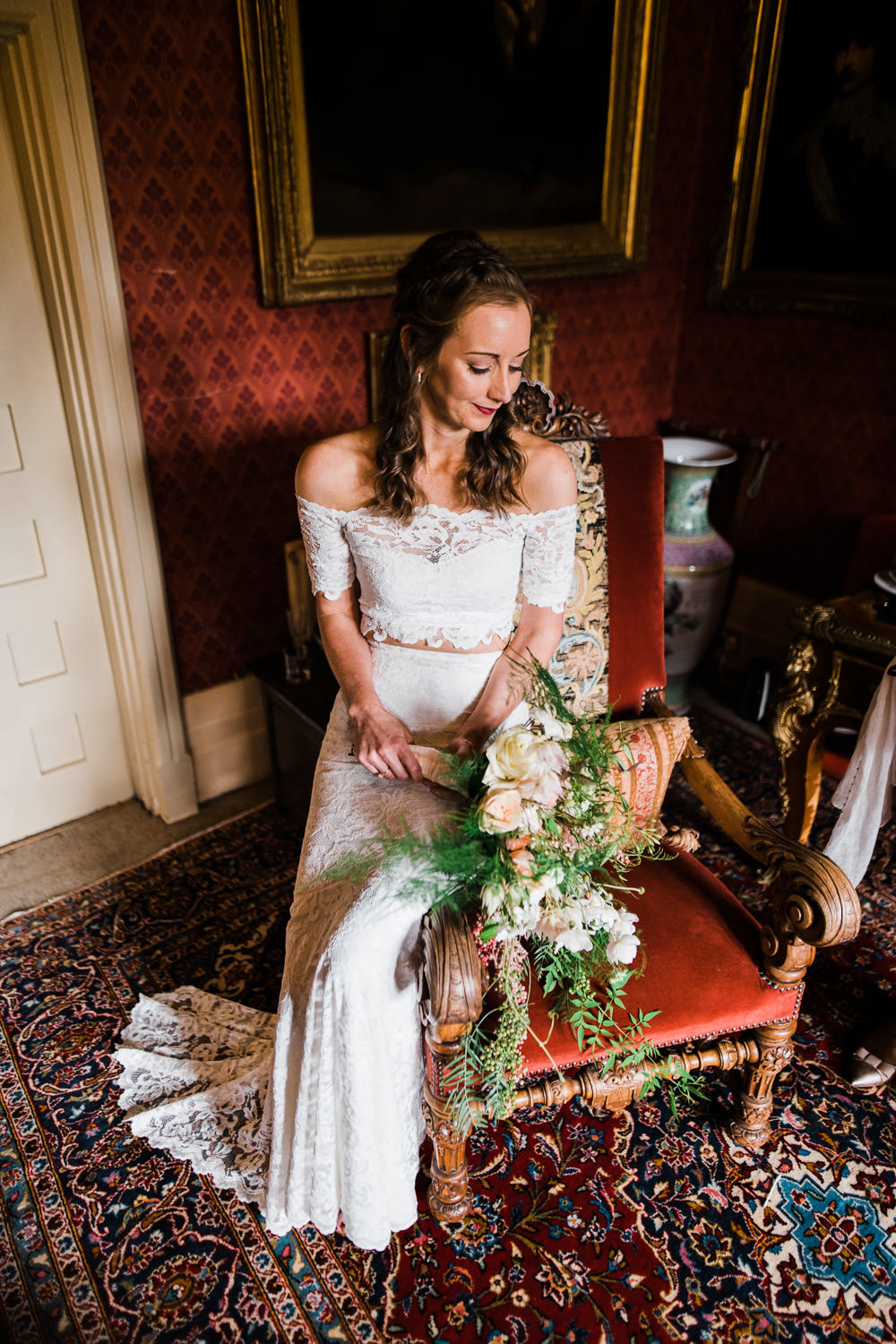 bride sat on red chair holding flowers