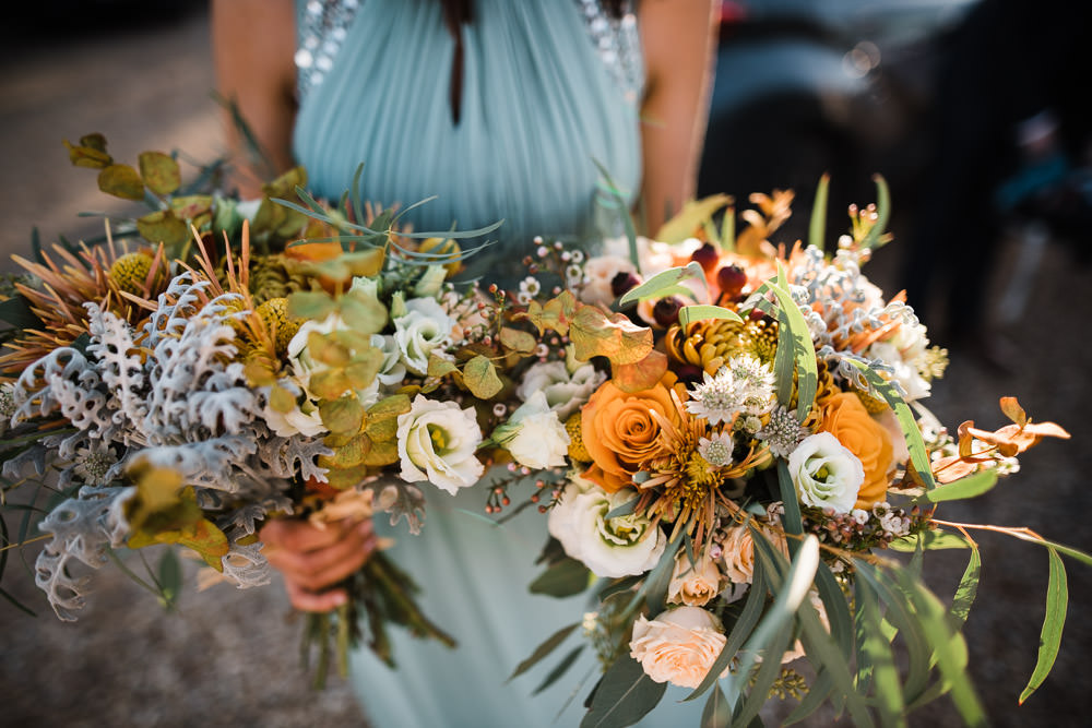 two large bunches of orange wedding flowers