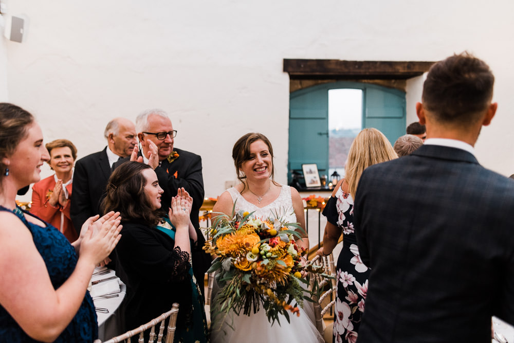 bride holding large flowers and smiling