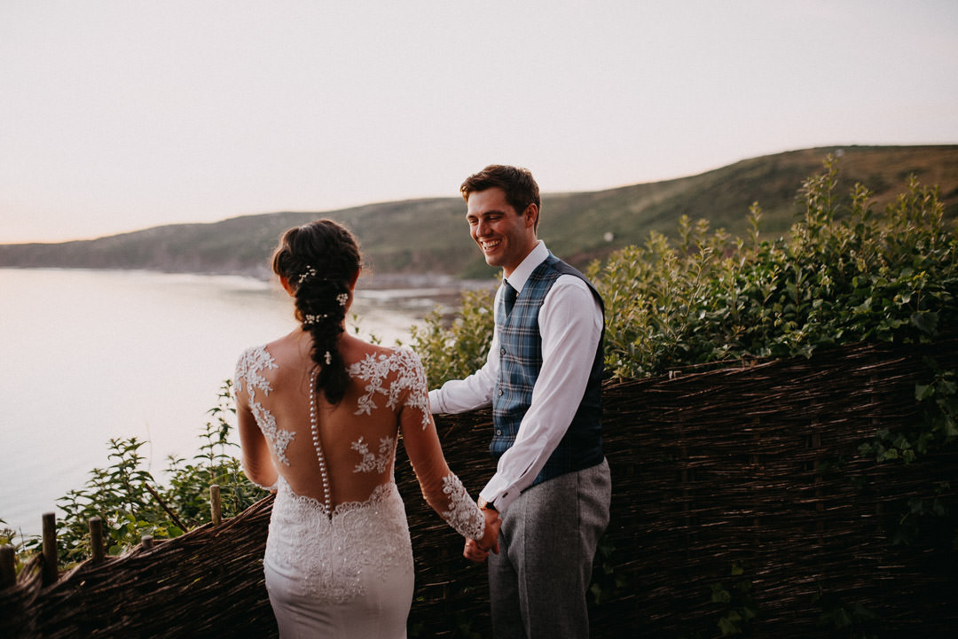 bride in white lace dress stood looking out to sea on hill