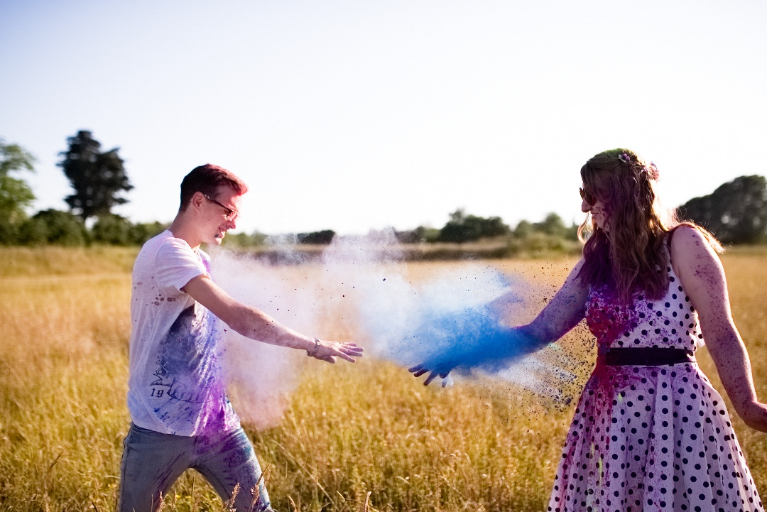 boy and girl throwing red and blue powdered paint in field