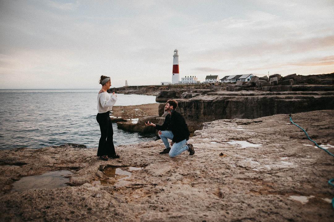 man proposing to woman on beach near lighthouse