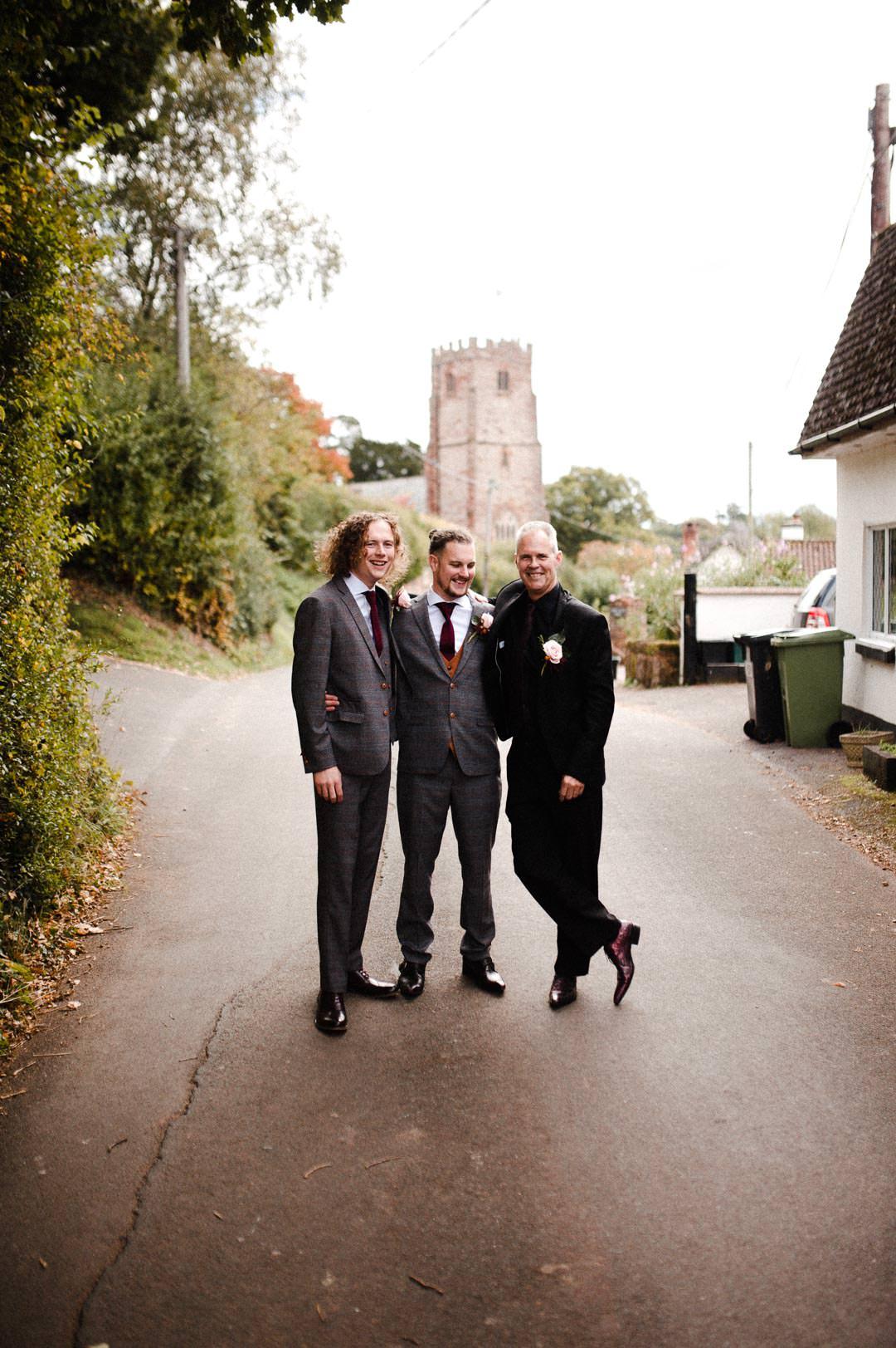 groom and best men at wedding stood in street