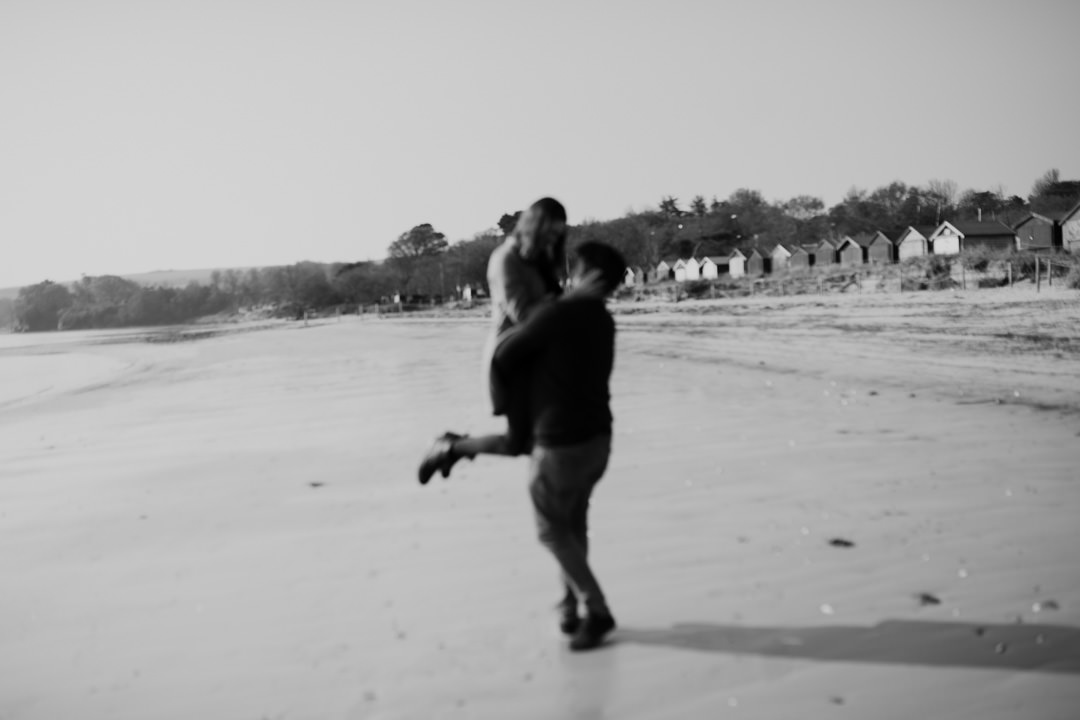 man lifting up girl on beach and smiling